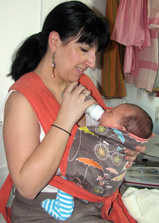 Μαμά ταΐζει το μωρό της με το μπιμπερό σε μάρσιπο mei tai