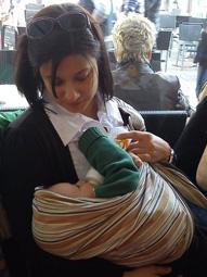 Μαμά που ταΐζει το μωράκι της με μπιμπερό στην αγκαλιά της