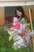 Κηπουρική με το μωρό ασφαλές στην αγκαλιά
