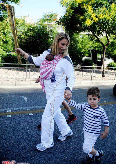 Η Σοφία Μπεκατώρου με μάρσιπο Αστεράκι Sling και το νεογέννητο μωρό της κρατά την Ολυμπιακή φλόγα