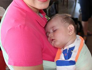 tired baby sleeping in sling
