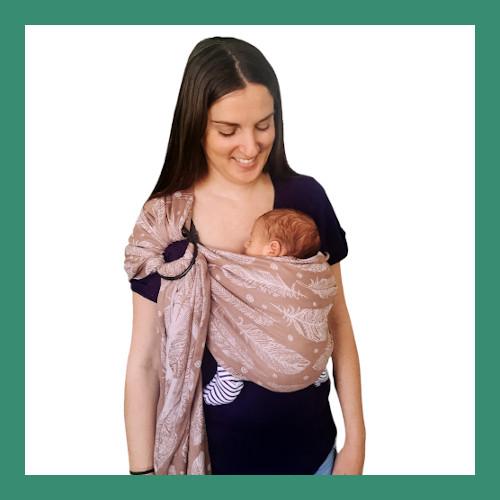 Μαμά φοράει νεογέννητο πολύ μικρό μωράκι που κοιμάται σε μάρσιπο ring sling